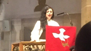 Pastor Elle preaches from a pulpit. There is a red banner with a white dove on the pulpit.