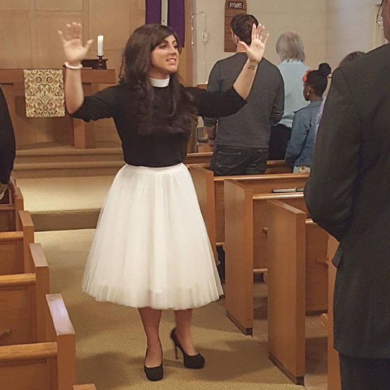 Pastor Elle blesses people during worship. She is a white woman with long brown hair. She is wearing a white tulle skirt and a black clergy shirt with black heels.