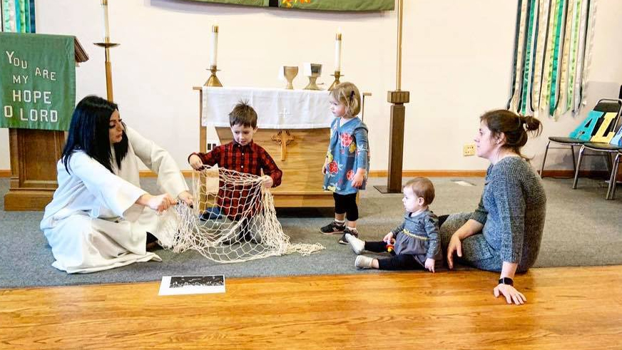 Pastor Elle and a child with short, brown hair hold up a net during a children's sermon. Two children and a parent watch.